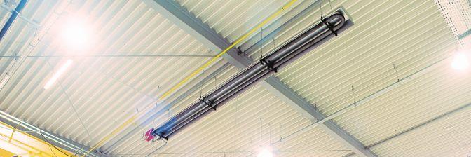Dlhý trubkový žiarič Schwank pod stropom budovy.
